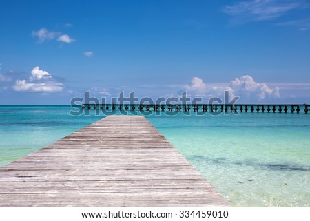 Wooden pier on tropical beach with turquoise water - stock photo