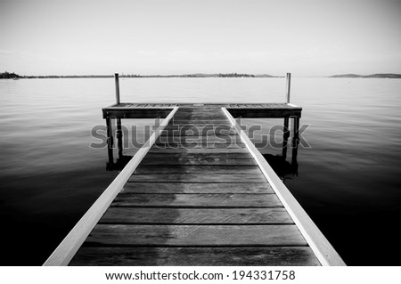 Wooden pier or jetty in black and white - stock photo
