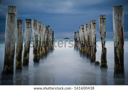Wooden pier or jetty remains on a beach looking out to the pacific ocean, Dunedin, New Zealand - stock photo