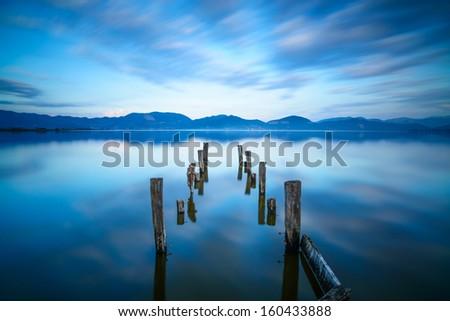 Wooden pier or jetty remains on a blue lake sunset and cloudy sky reflection on water. Long exposure, Versilia Massaciuccoli Lake, Tuscany, Italy. - stock photo