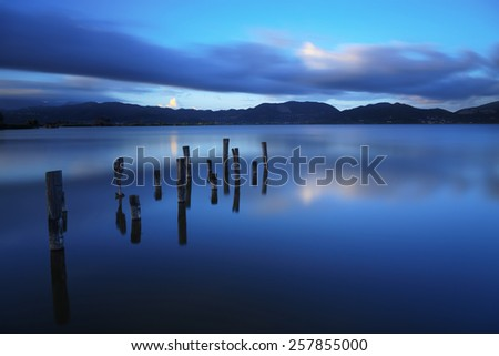 Wooden pier or jetty remains on blue lake sunset and sky reflection water. Long exposure, Versilia Massaciuccoli, Tuscany, Italy. - stock photo