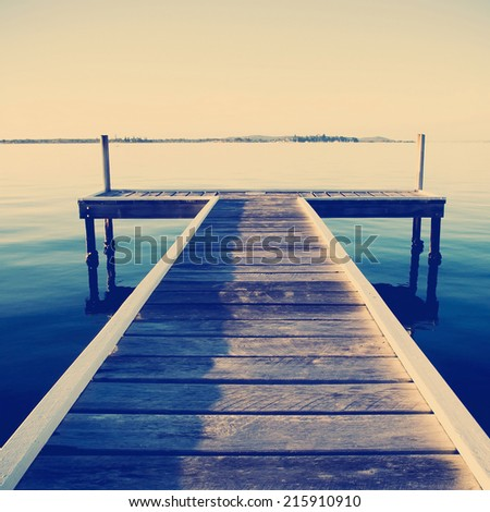 Wooden pier or jetty stretches out into an idyllic ocean with Instagram style filter - stock photo