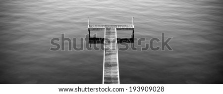 Wooden pier or  jetty stretches out into ocean in black and white panorama - stock photo