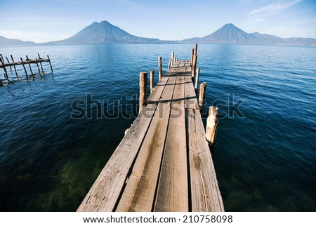 Wooden pier stretching to the horizon and volcanoes in the background - stock photo