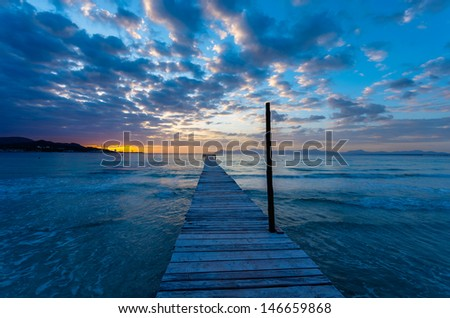 Wooden pier sunrise sea view clouds sky horizon idyllic scene, Alcudia beach, Majorca island, Spain - stock photo