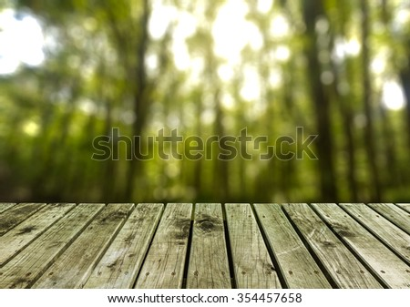 wooden pier with blurry forest background