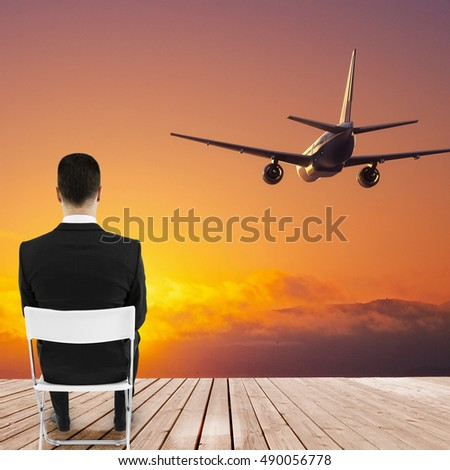 Wooden pier with businessman sitting on chair and looking at beautiful sunset view and a flying by airplane. Travel concept
