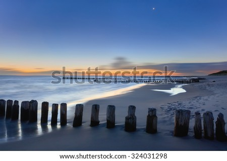 Wooden piles dipping into the ocean on sandy beach at sunset. Hel Peninsula, Baltic sea, Poland - stock photo