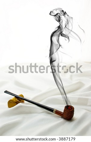 Wooden pipe on satin with drifting smoke in the shape of a beautiful woman. - stock photo