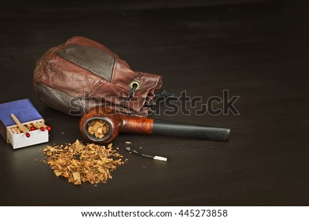 Wooden pipe with tobacco on a black background. Old tobacco pipe and spilled tobacco.