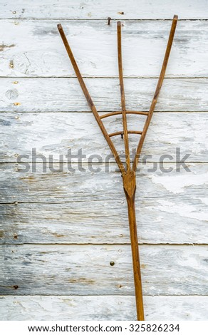 Wooden pitchfork on a white wall
