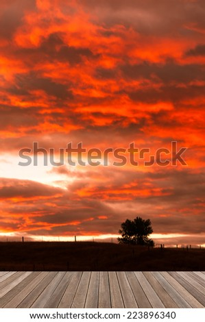 wooden plank platform on silhouette prairie background with awesome morning sky - stock photo