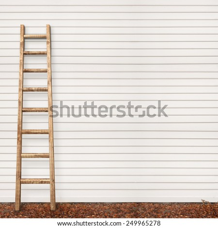 wooden plank wall and the ladder, ground covered with fallen leaves - stock photo