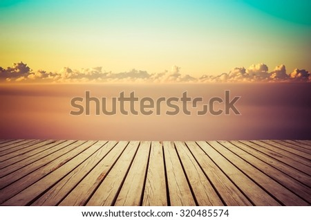 Wooden planks floor with sunrise sky in the background.