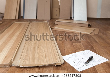Wooden planks, manual and a screwdriver laying on the floor - stock photo
