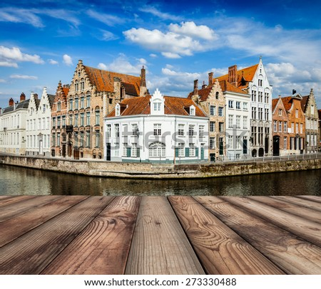 Wooden planks with European view of  Bruges canal and old historic houses of medieval architecture in background. Brugge, Belgium - stock photo