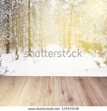 wooden planks with snowed winter forest background - stock photo