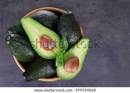 Wooden plate full of avocados on a black background - stock photo