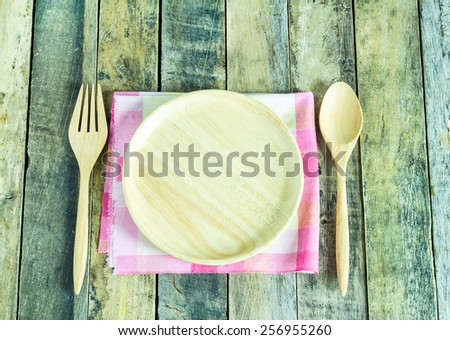 Wooden plate spoon and fork on wooden table background - stock photo