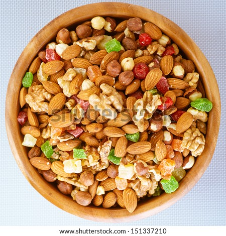 Wooden plate with variety of ingredients - almonds, walnuts, hazelnuts and candied fruit, on tablecloth. - stock photo