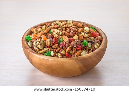 Wooden plate with variety of ingredients - almonds, walnuts, hazelnuts and candied fruit, on table. - stock photo