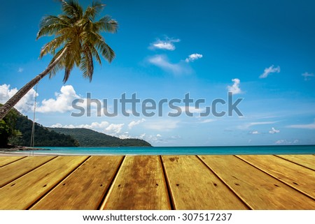 wooden platform beside blue sky and tropical beach with coconut palm tree.