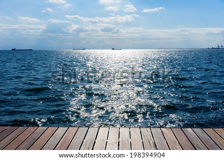 Wooden platform beside the ocean and blue sky - stock photo