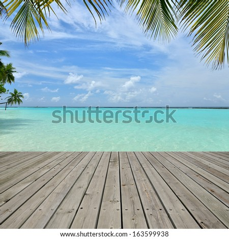 Wooden platform beside tropical beach with palm tree leaf  - stock photo