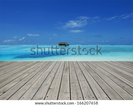 Wooden platform beside tropical lagoon -- Overwater bungalow on tropical lagoon - stock photo