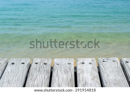 Wooden platform beside water sea background - stock photo