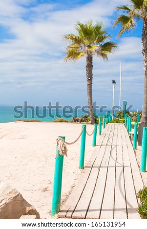 Wooden platform on way to sea of palm trees in the white beach - stock photo