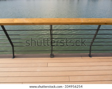Wooden platform with an iron railing above the river