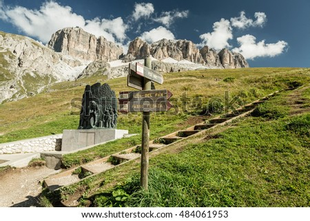 Wooden pointer for hikers in the Dolomites. Piz Boe with beautiful blue sky,  Dolomiten mountains, Italien Alps.  Travel concept.