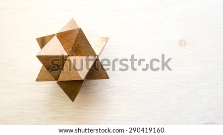 Wooden pointy cube puzzle on wooden surface. Concept of complex and smart logical thinking. Slightly defocused and close up shot. Copy space. - stock photo