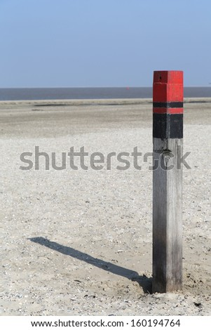 Wooden pole at the beach in Texel - Netherlands - stock photo