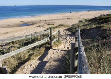 Wooden pole steps leading down  to Ocean Beach Bunbury Western Australia  on a sunny early morning in early autumn cast shadowy patterns on the sand. - stock photo