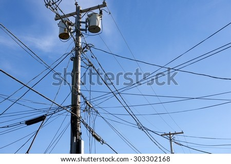 Wooden Poles with Power Lines and Telephone Lines Against the Sky (Rockport, Massachusetts, USA / June 7, 2015) - stock photo