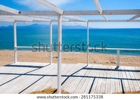 Wooden porch on the beach looking to the sea - stock photo