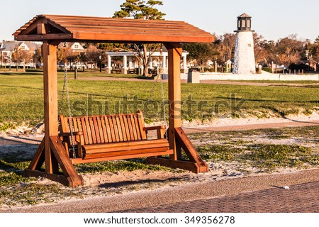 Wooden porch swing at Buckroe Beach in Hampton, Virginia with the lighthouse in the background. - stock photo