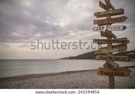 Wooden post with many written signs of different destinations in all directions, in a cloudy day,  Cala Codolar, Ibiza, Balearic Islands, Spain - stock photo
