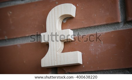 Wooden pound sterling symbol on a brick wall - stock photo