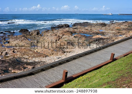 Wooden promenade with bench and rocky shore of the Atlantic Ocean in Porto, Portugal. - stock photo