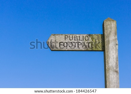 Wooden Public Footpath sign against a clear blue sky.
