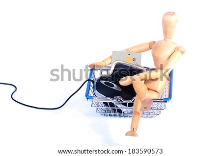 Wooden puppet sitting easy in a shopping basket with a computer mouse and a credit card in a wallet to buy things on the internet