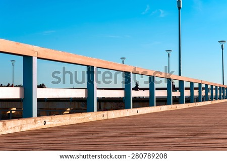 Wooden quayside in rays of evening sunlight. Multicolored outdoors image on a blue sky background.