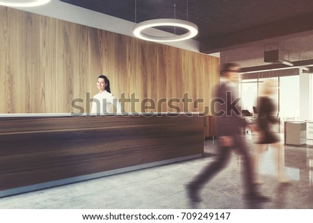Wooden reception desk is standing in a modern office with a concrete floor, light wooden walls and round ceiling lamps. Open space room background. Side view, people. 3d rendering mock up toned image