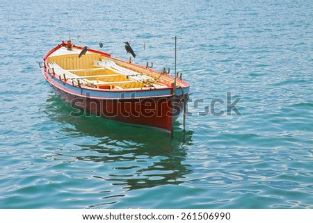 Wooden red boat in a calm lake - stock photo