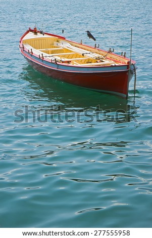 Wooden red boat in a calm lake - image with copy space - stock photo
