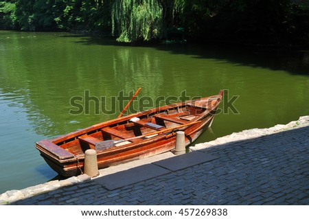 wooden red boat on green water - stock photo