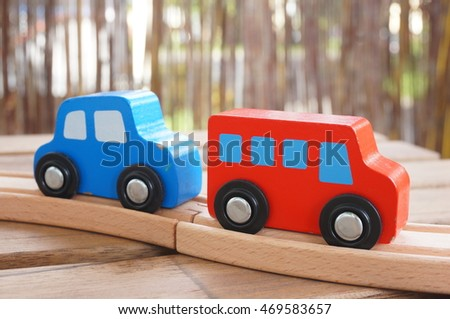 Wooden red toy bus and blue wooden toy car on a track